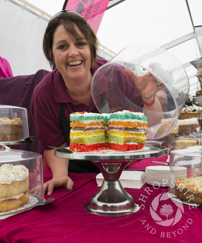 Louise Gough of Handmade In Ludlow showing off a colourful rainbow cake at the 2014 Ludlow Food Festival, Shropshire, England.
