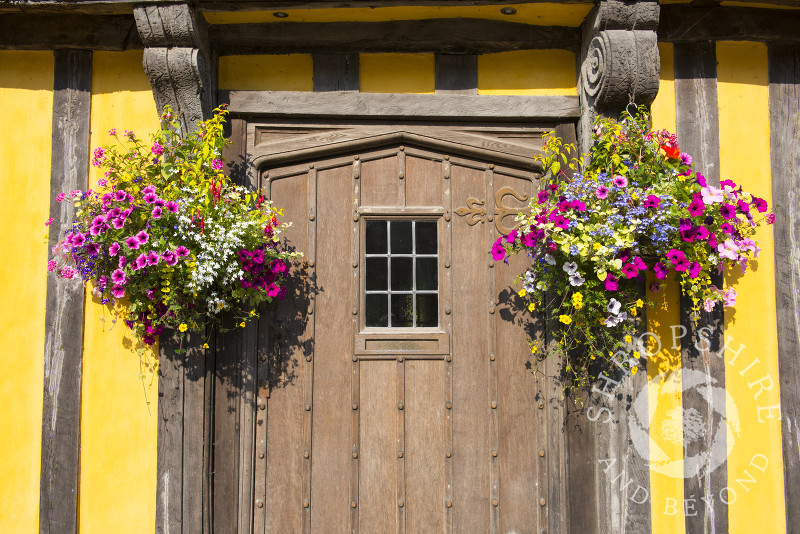 Hanging baskets adorn the front door of a half-timbered house in Broad Street, Ludlow, Shropshire, England.