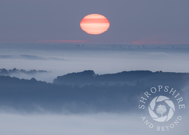 The sun rising over Wolverhampton, seen from Caradoc, Shropshire, with Wenlock Edge.
