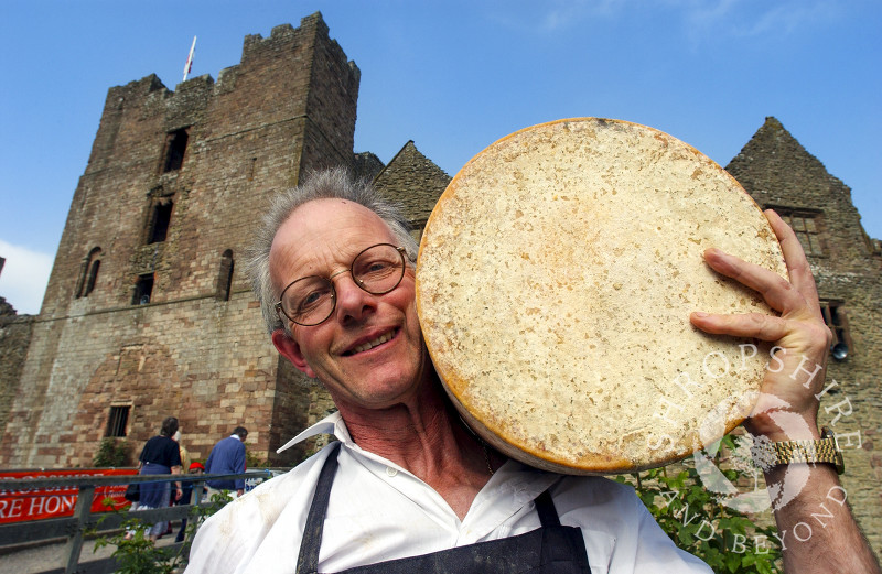 A vendor holds a cheese wheel in the grounds of Ludlow Castle during Ludlow Food Festival, Shropshire, England.