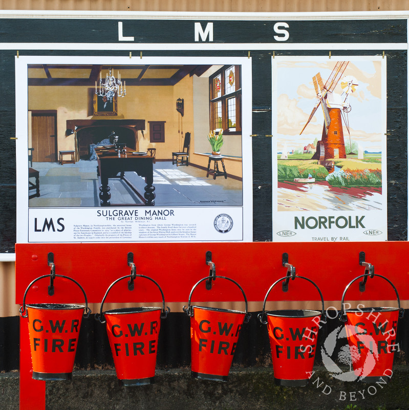 Fire buckets and vintage advertising signs on the platform at Hampton Loade station, Severn Valley Railway, Shropshire, England.