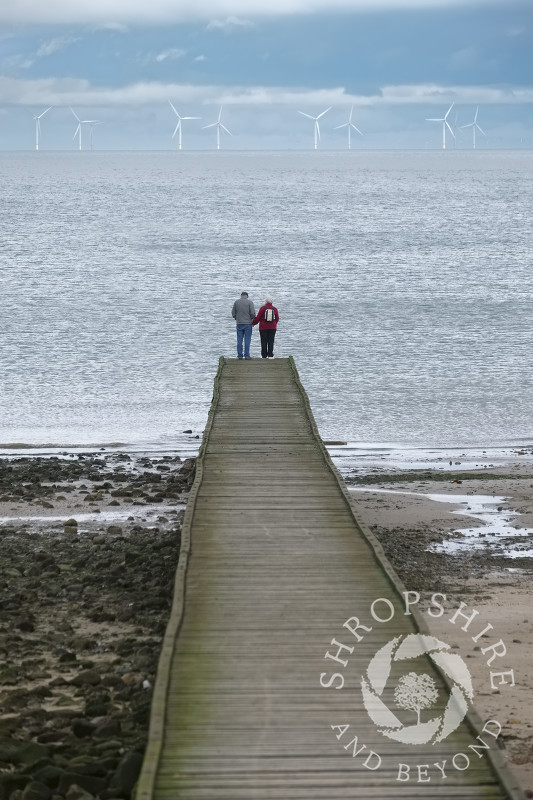 An elderly couple look out across the sea towards Gwynt y Mor wind farm from a jetty at Llandudno, Conwy, Wales.