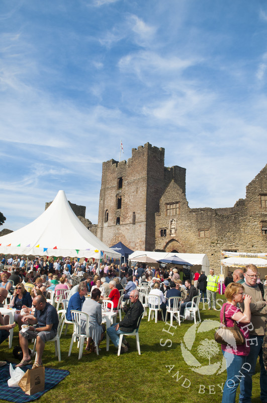 Visitors enjoy refreshments in the castle grounds during the Ludlow Food Festival, Shropshire, England.