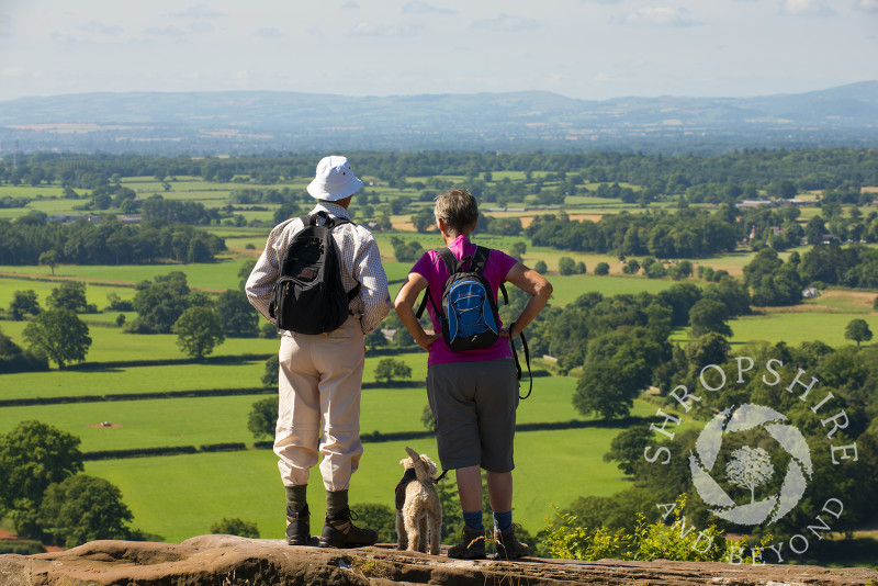 Two walkers and their dog look out over the north Shropshire landscape from Grinshill Hill, Shropshire, England.