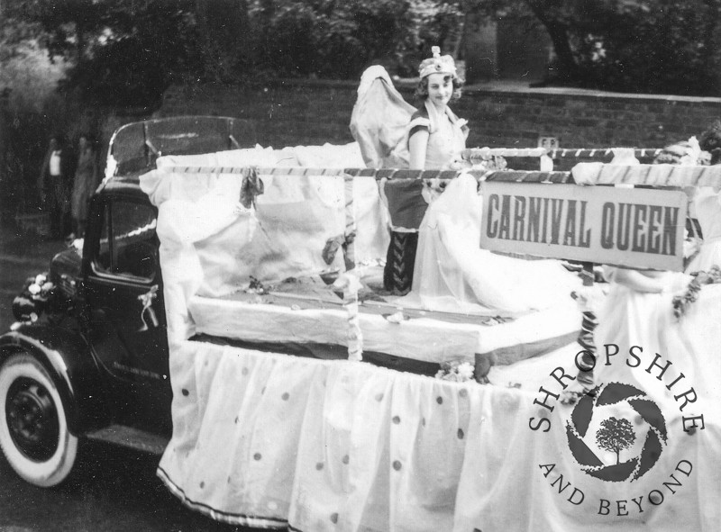 Carnival Queen float in Church Street, Shifnal, Shropshire, during the annual carnival, 1950s.