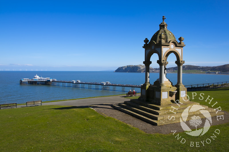 Victorian drinking fountain in Happy Valley Gardens looking to Llandudno Pier, North Wales.
