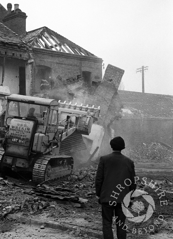 A passer-by watches as buildings are demolished in Bradford Street, Shifnal, Shropshire, in 1966.