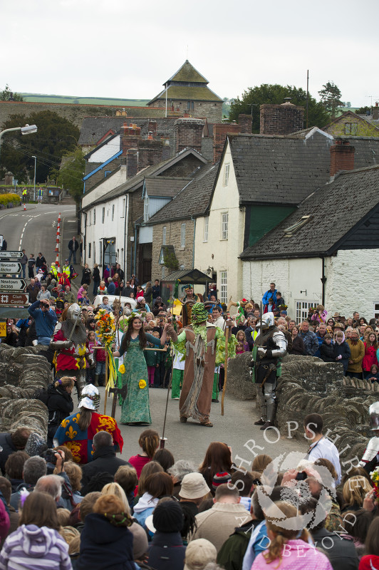 The Green Man and the May Queen in procession over the bridge at Clun Green Man Festival, Shropshire.