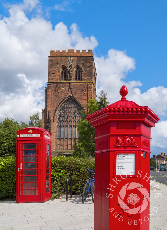 Shrewsbury Abbey with a red phone box and Penfold pillar box, Shropshire.