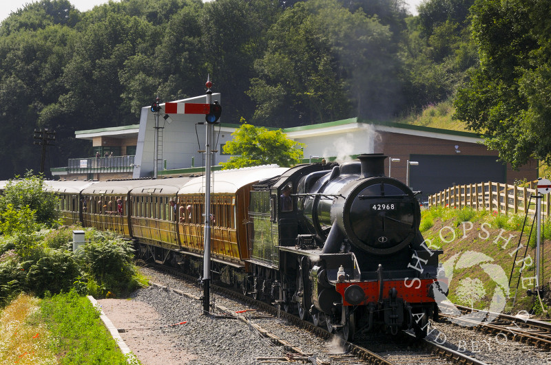An LMR Stanier steam locomotive enters Highley Station past the Engine House, Severn Valley Railway, Shropshire, England.
