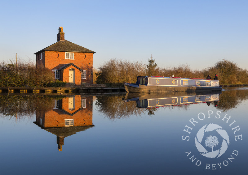 A canal boat passes a house on the Llangollen branch of the Shropshire Union Canal at Whixall, Shropshire.