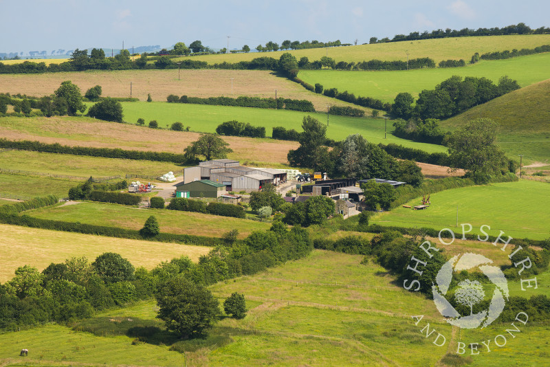 A farm nestles amid rolling countryside near Hopesay, Craven Arms, Shropshire, England.