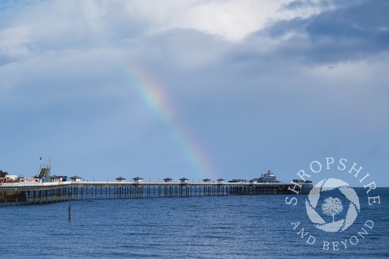 Rainbow and rain clouds over the pier at Llandudno, Conwy, Wales.