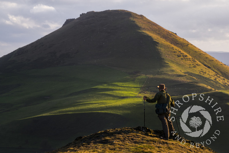 A walker enjoys the view of Caer Caradoc seen from the Lawley, Shropshire.