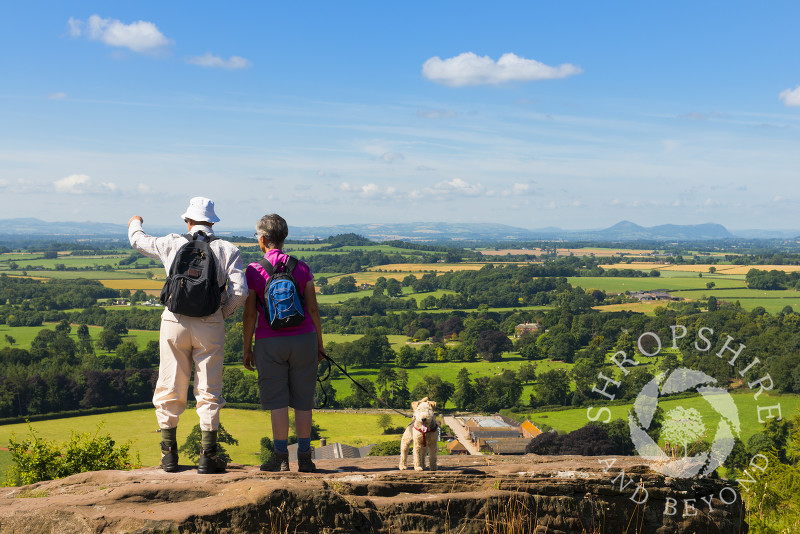 A pair of walkers, accompanied by their dog, look out over the north Shropshire countryside from Grinshill Hill, Shropshire, England