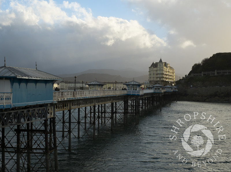 Looking along Llandudno Pier towards the Grand Hotel and the Victorian promenade at Llandudno, Wales.