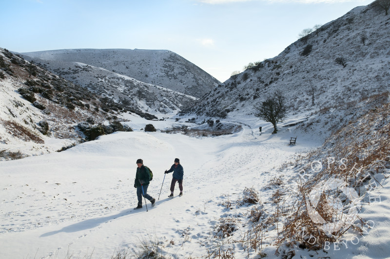 Winter walkers in the snow at Carding Mill Valley, near Church Stretton, Shropshire, England.