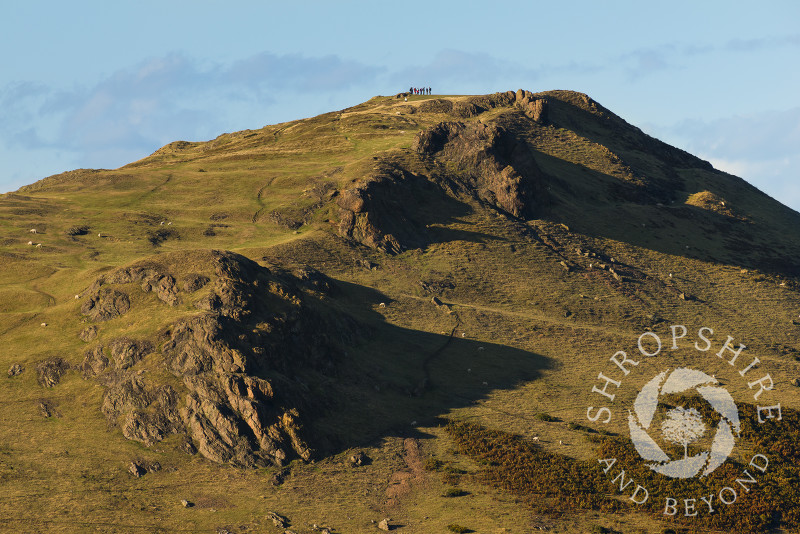 A group of walkers standing on the summit of Caer Caradoc, near Church Stretton, Shropshire, England.