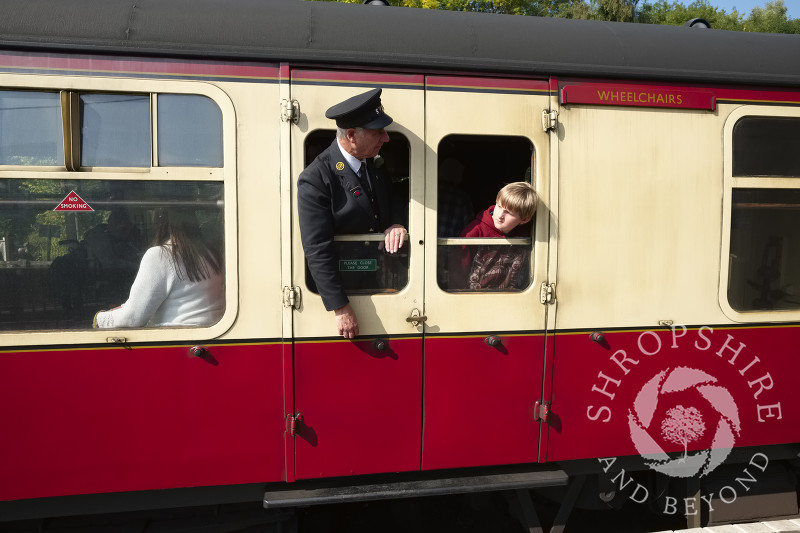 Guard and young passenger looking out of carriage windows at Highley Station, Shropshire, on the Severn Valley Railway heritage line.