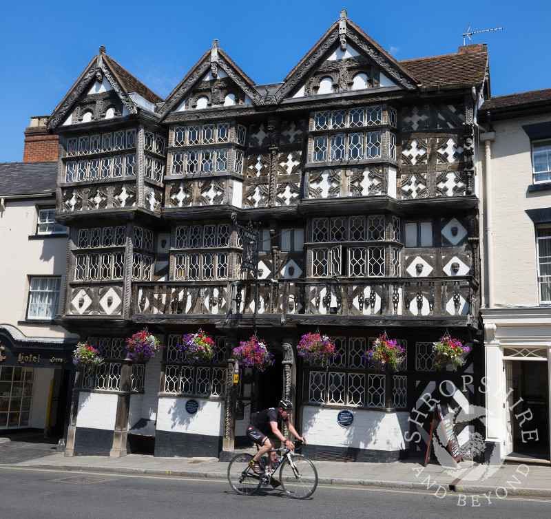 A cyclist rides past the Feathers Hotel at Ludlow, Shropshire, England.