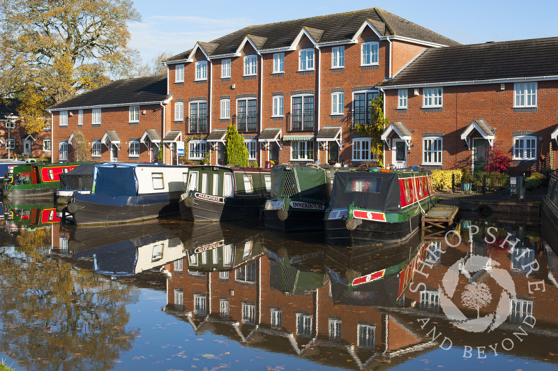 Canal boats and homes reflected in the Shropshire Union Canal at Market Drayton, Shropshire, England.