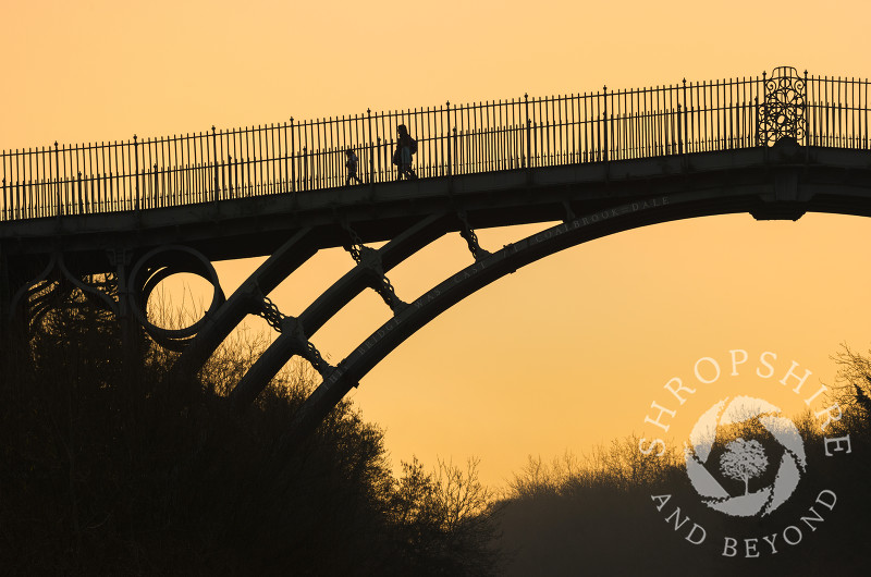 Walkers at sunrise on the Iron Bridge at Ironbridge, Shropshire.