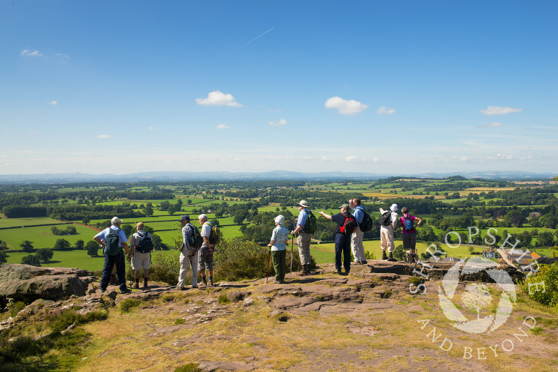 A group of walkers look out over the north Shropshire landscape from Grinshill Hill, Shropshire, England.