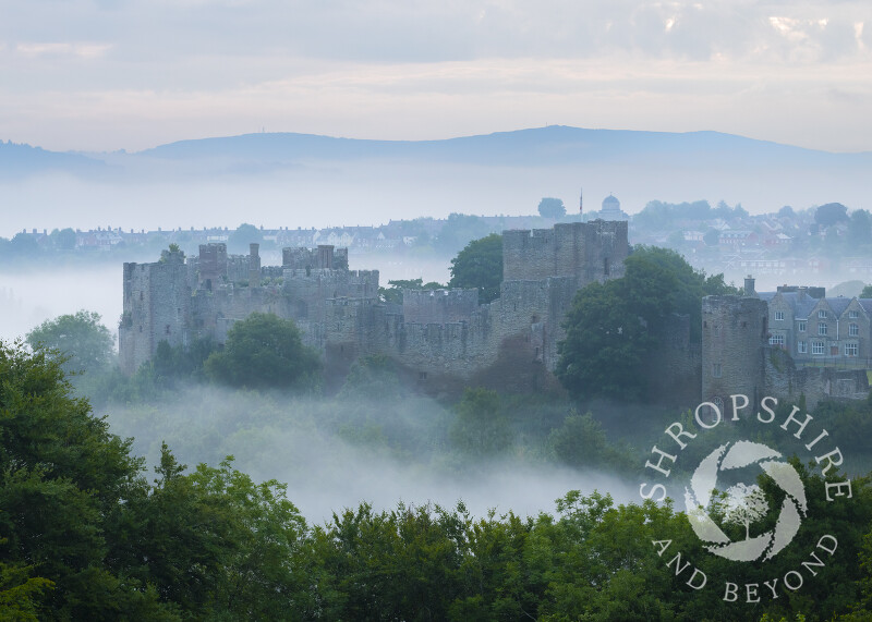 Mist swirls arounds Ludlow Castle at dawn, Shropshire.