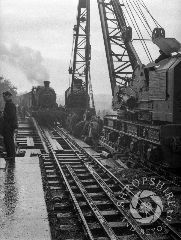 A steam train passes two cranes on the railway bridge, Shifnal, Shropshire, 1953.