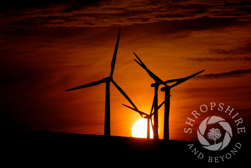 Wind turbines silhouetted against the sunset at Carno Wind Farm in Powys, Mid Wales.