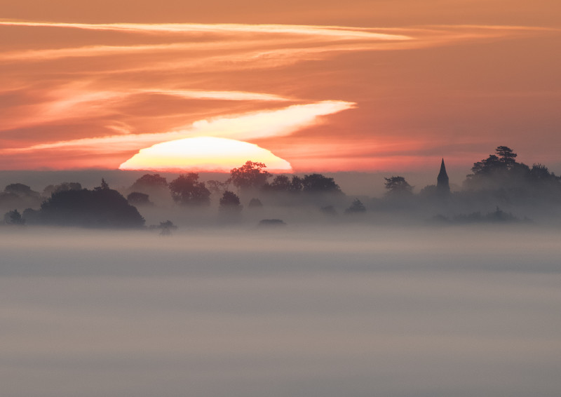Sunrise near Welsh Frankton Church, seen from Old Oswestry Hill Fort.