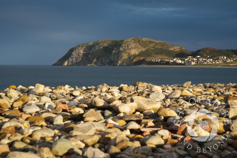 Autumn sunlight on the beach and Little Orme at Llandudno, Conwy, Wales.