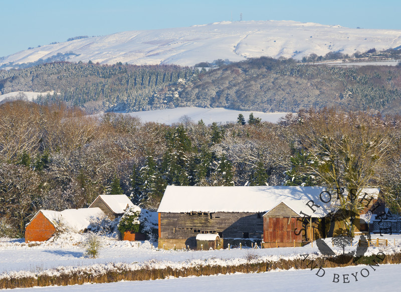 Snow surrounds an old barn near Bromfield beneath Brown Clee Hill, Shropshire.