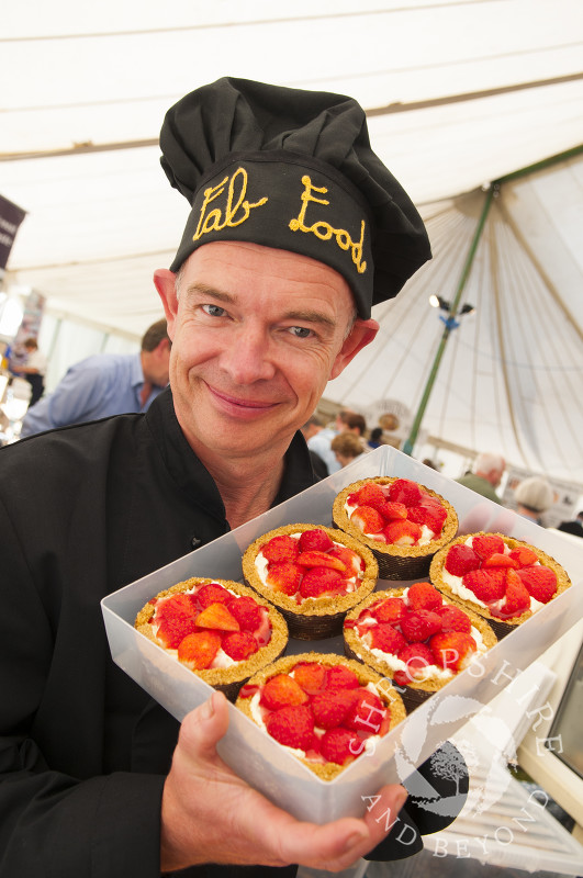 A vendor with a batch of strawberry tarts at Ludlow Food Festival, Shropshire, England.