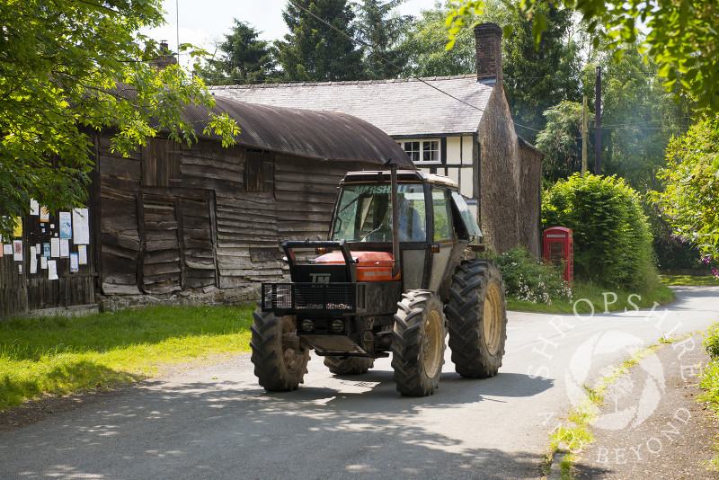 A tractor passes through the village of Hopesay near Craven Arms, Shropshire, England.