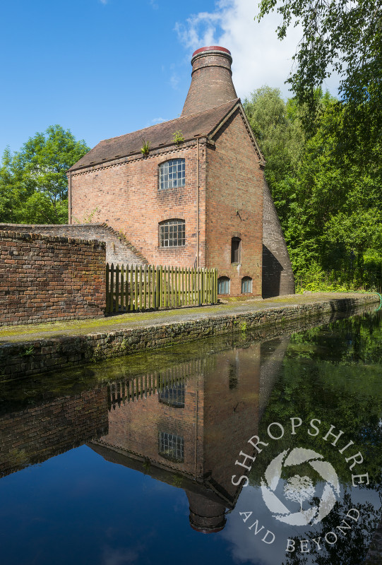 The Coalport China Museum, one of the Ironbridge Gorge Museums, reflected in the water of the Shropshire Canal at Coalport, Shropshire.