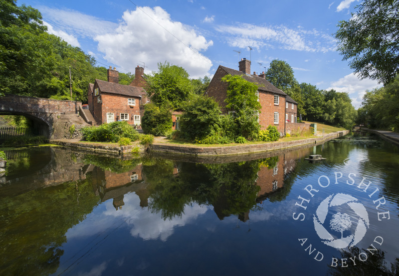 Cottages reflected in the Shropshire Canal at Coalport, Shropshire, England.