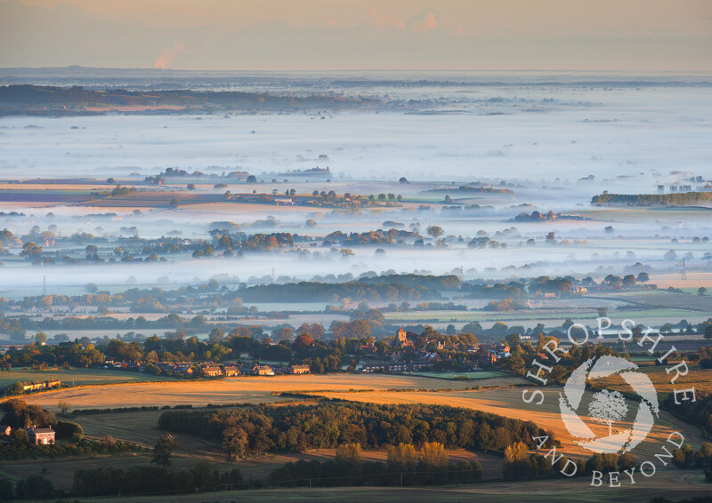 Autumn mist rolls across the Shropshire landscape beyond the village of Wrockwardine, seen from the summit of the Wrekin, England.