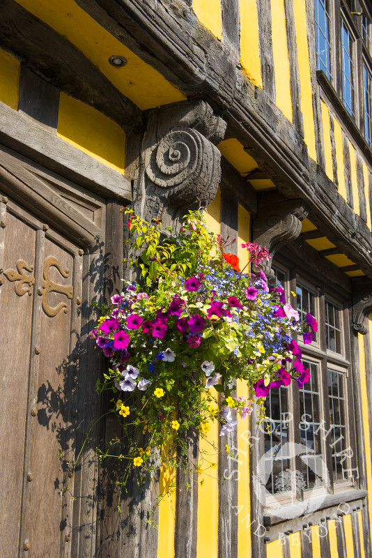 Flowers in a hanging basket outside a half-timbered house in Broad Street, Ludlow, Shropshire, England.