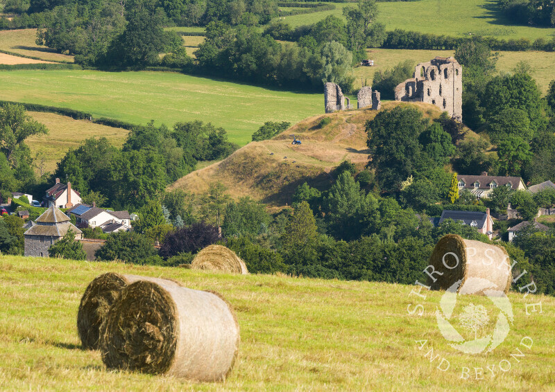 Hay bales in a field overlooking Clun and its castle, Shropshire.