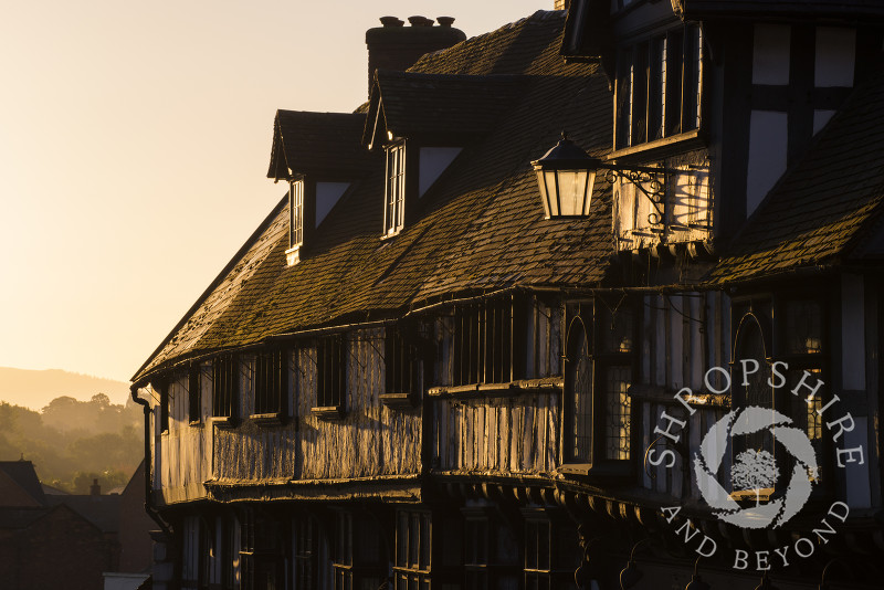 Sunrise illuminates half-timbered buildings on Wyle Cop, Shrewsbury, Shropshire.