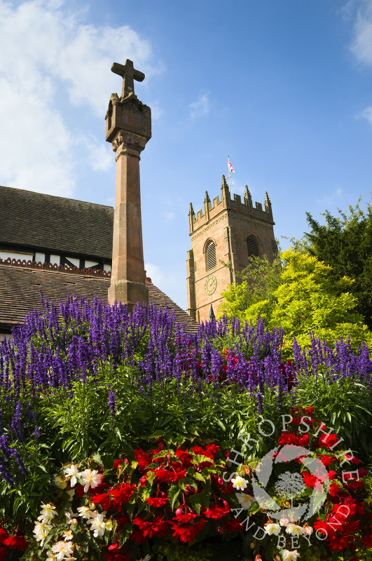 Flowers surround the 14th century cross at the entrance to All Saints Church, Claverley, Shropshire, England.