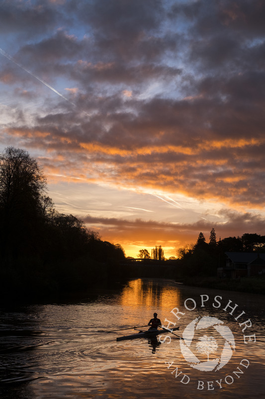 A rower at sunrise on the River Severn at Shrewsbury, Shropshire.