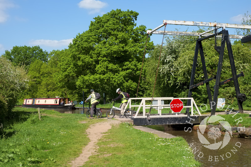 Cyclists cross the Llangollen Canal on the lift bridge at Whitchurch, Shropshire.