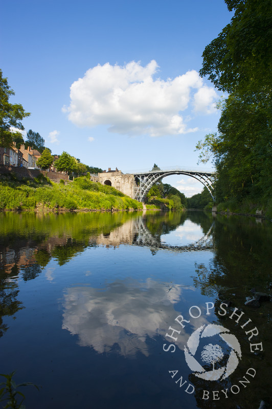 Blue sky and clouds above the Iron Bridge reflected in the River Severn at Ironbridge, Shropshire, England.