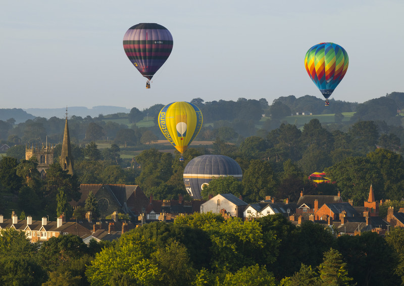 Hot air balloons lift off during the annual Oswestry Balloon Carnival, seen from Old Oswestry Hill Fort, Shropshire.