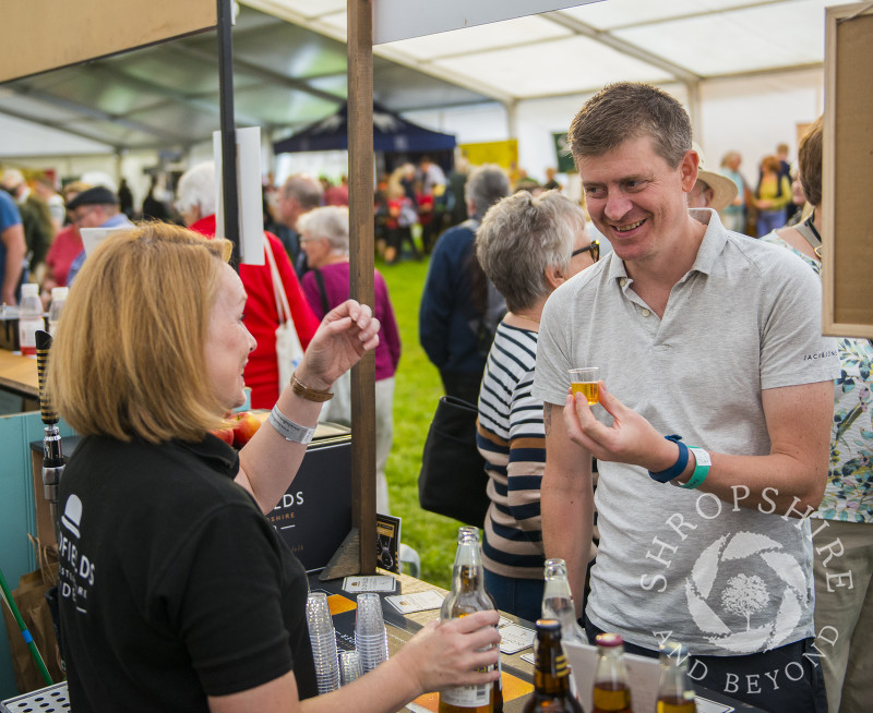 A visitor samples Oldfields cider at Ludlow Food Festival, Shropshire.
