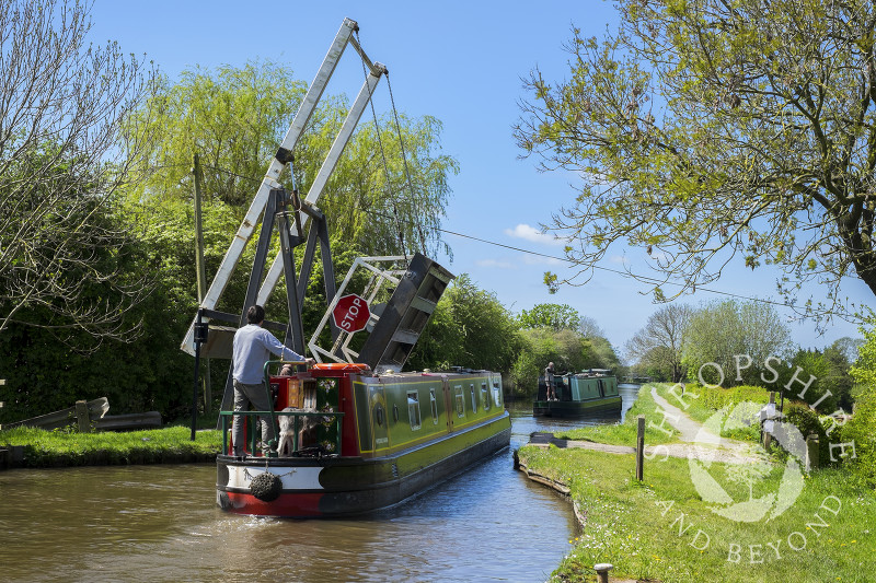A narrowboat negotiates Morris's Lift Bridge on the Llangollen Canal near Whixall Moss, Shropshire.
