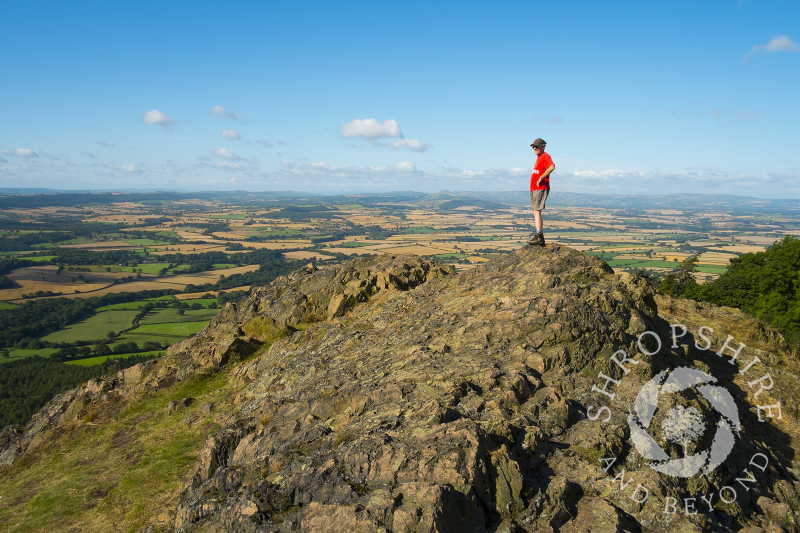 A man standing on top of the Wrekin looking out over Shropshire, England.