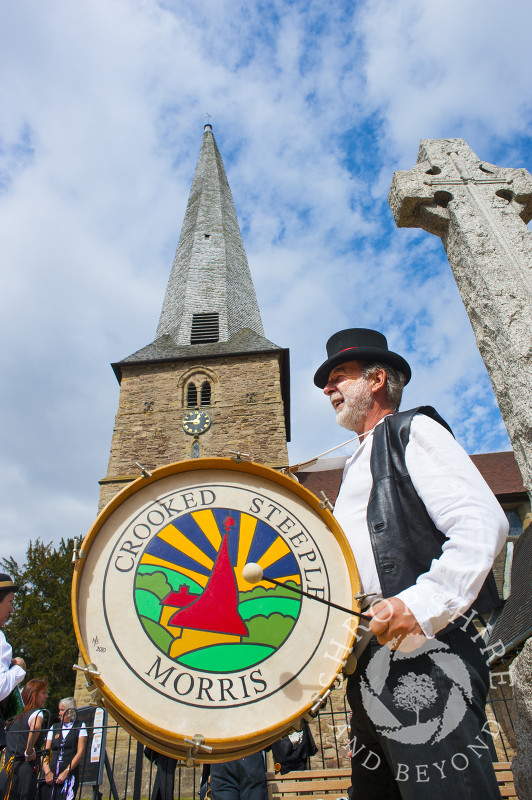 Crooked Steeple Morris dancer in front of St Mary's Church with its twisted spire at Cleobury Mortimer, Shropshire, England.